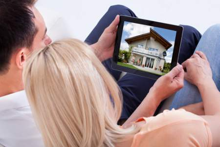 man and woman looking at house on a tablet