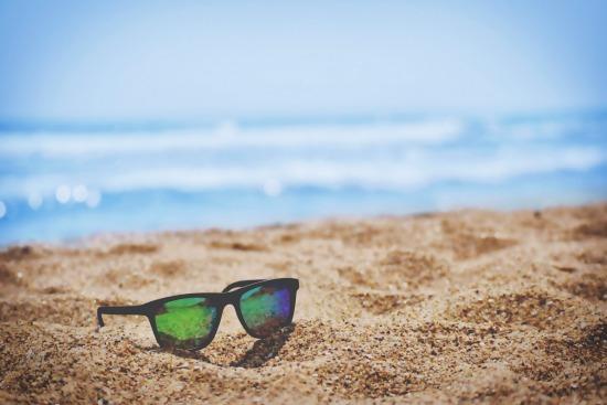 Sunny beach with sunglasses on sand
