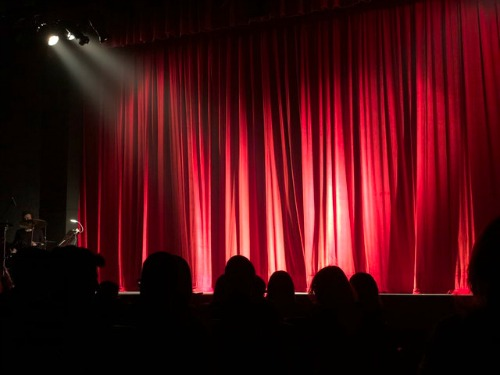 red stage curtain with lights shining
