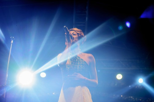 woman singing with blue lights shining