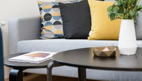 grey sofa with yellow and black pillows