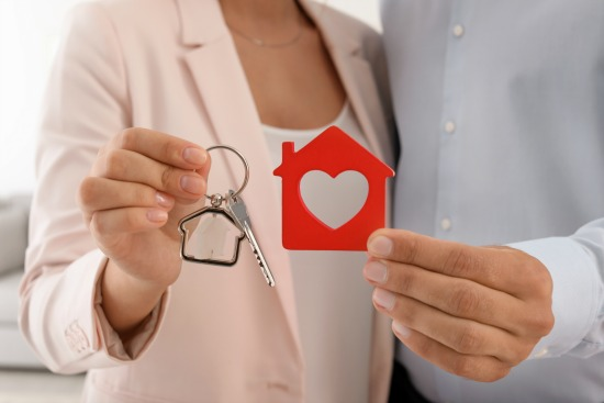 couple holding red house and keys