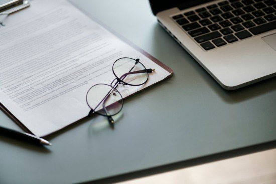paperwork with glasses and laptop