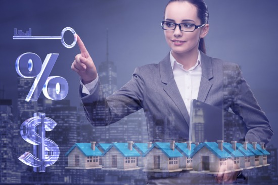 interest rate concept with woman pointing to key over percentage sign, dollar sign, and homes