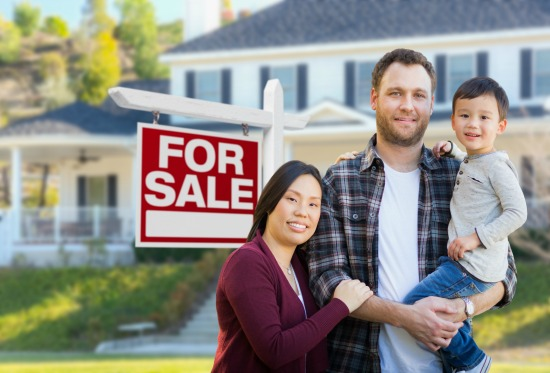 Family in front of for sale sign