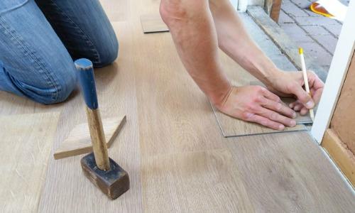 renovations - man working on floor tile