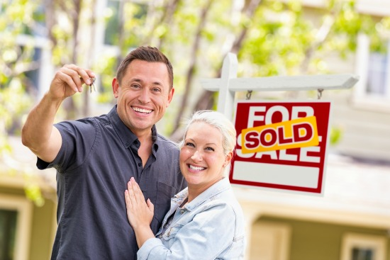 couple holding house keys in front of sold sign