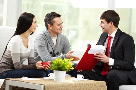couple with mortgage loan agent holding red clipboard