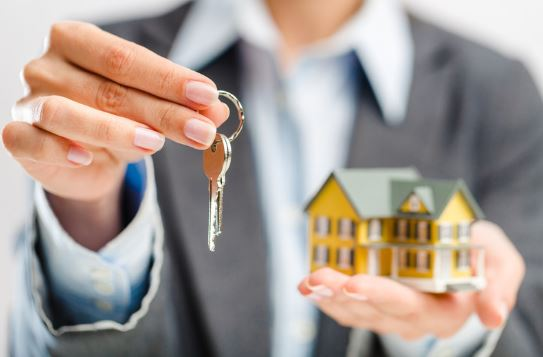 Real estate agent holding a toy house and keys