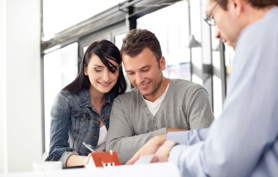 Couple signing paperwork to buy house