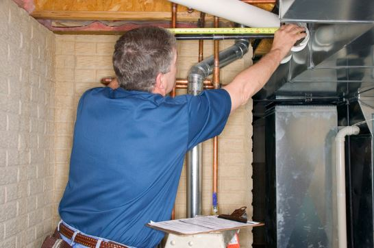 man inspecting HVAC system
