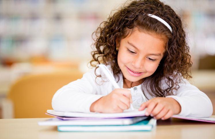 Elementary school girl writing in notebook