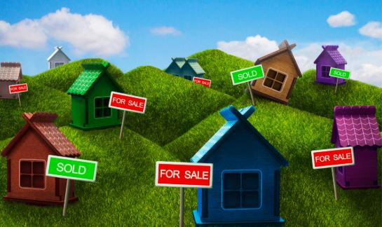 Different colored wood houses with sale signs