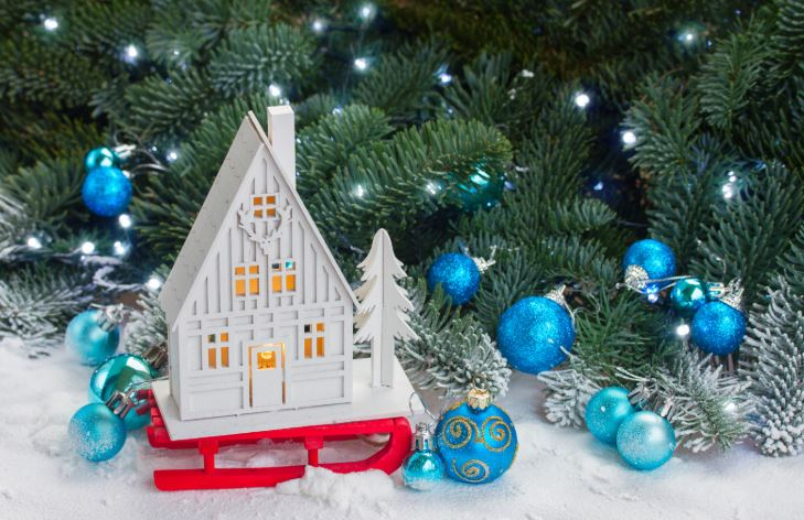 White toy house on red sleigh under tree