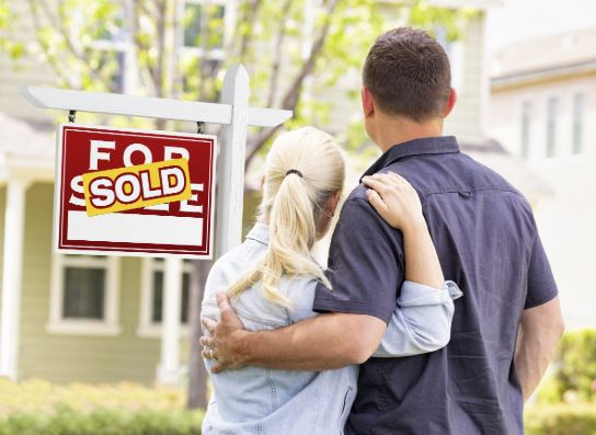 Couple standing in front of sold sign