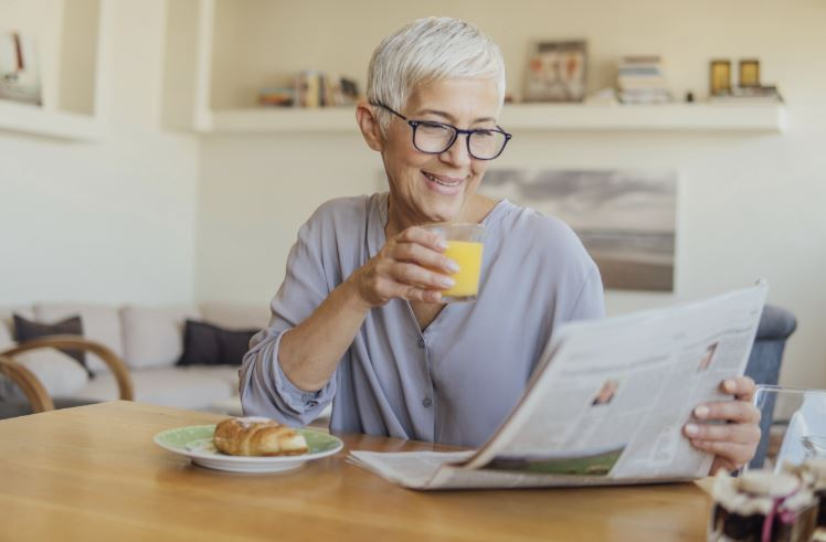 Woman reading newspaper ad for house