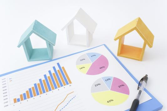 Houses sitting near real estate chart paper