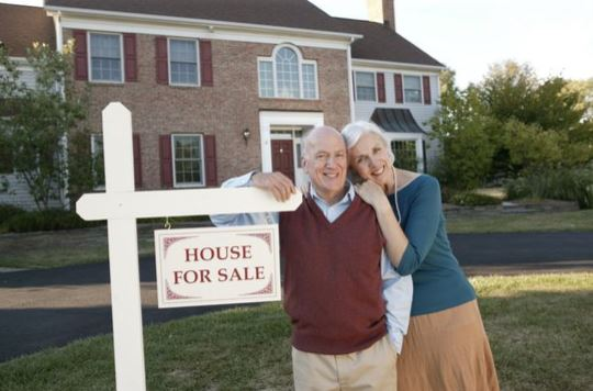 Older couple standing at for sale sign