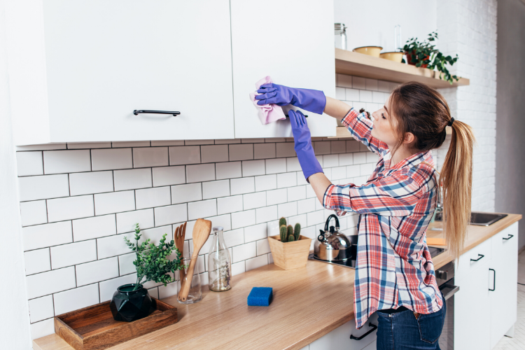 home inspection tips for sellers - clean the house - woman cleaning kitchen cabinet